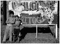 Children in front of a turtle a shark sign in Vaitogi. Tutuila, American Samoa (black and white)