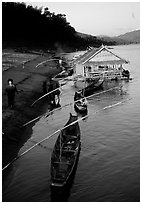 Boats and stilt house of a small hamlet. Mekong river, Laos (black and white)