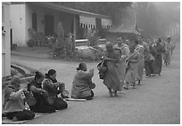 Women line up to offer alm to buddhist monks. Luang Prabang, Laos ( black and white)