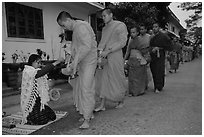 Buddhist monks receiving alm from woman. Luang Prabang, Laos ( black and white)