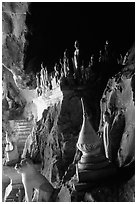 Buddhist statues left by pilgrims, lower Pak Ou cave. Laos (black and white)