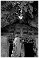 Novice Buddhist monk at entrance of lower Pak Ou cave. Laos (black and white)