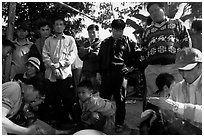 Coaches take care of wounded roosters after fighting. Luang Prabang, Laos ( black and white)