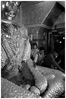 Adding golden leaves to the venerated Mahamuni image. Mandalay, Myanmar (black and white)