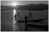 Intha fishermen on long flat-bottomed boats at sunset. Inle Lake, Myanmar ( black and white)