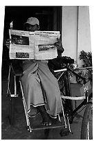 Cyclo driver reading newspaper with picture of QT Luong tour group. Bago, Myanmar ( black and white)