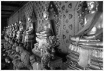 Monks sitting below row of buddha images, Wat Arun. Bangkok, Thailand (black and white)