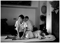 Traditional thai massage in traditional Thai medicine center of Wat Pho. Bangkok, Thailand (black and white)