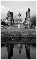 Buddha image reflected in moat, morning, Wat Mahathat. Sukothai, Thailand (black and white)