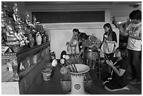 Worshippers with lotus inside Wat Saket. Bangkok, Thailand ( black and white)