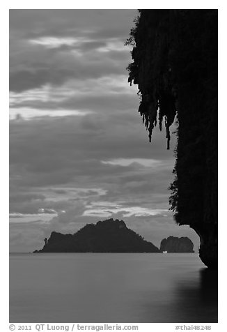 Limestone crag with stalactite, distant islet, boat light, Railay. Krabi Province, Thailand (black and white)
