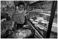 Woman adding spices to Pad Thai, Ko Phi-Phi island. Krabi Province, Thailand ( black and white)