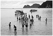 Asian tourists wading in water, Ko Phi Phi. Krabi Province, Thailand ( black and white)