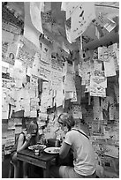 Women eating at Pad Thai restaurant decorated with customer notes, Ko Phi-Phi Don. Krabi Province, Thailand ( black and white)