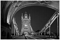 Arch and car traffic on the Tower Bridge at night. London, England, United Kingdom ( black and white)