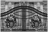 Entrance grids of Buckingham Palace with royalty emblems. London, England, United Kingdom (black and white)