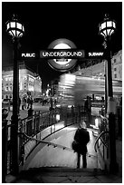 Man entering underground, and motion-blurred double decker bus,  Piccadilly Circus. London, England, United Kingdom ( black and white)