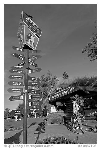 Sign Air Crossroads of the World, man on bicycle in front of visitor center. Anchorage, Alaska, USA