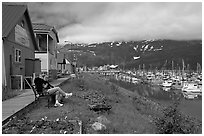 Couple sitting on bench by the harbor. Whittier, Alaska, USA (black and white)