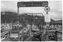 Ramp to harbor deck with Whittier sign. Whittier, Alaska, USA (black and white)