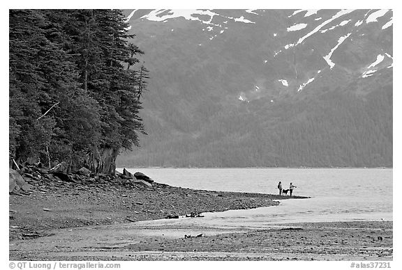 Women fishing and dog, at the edge of Passage Canal Fjord. Whittier, Alaska, USA (black and white)