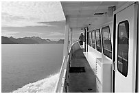 Passenger standing outside tour boat. Seward, Alaska, USA (black and white)
