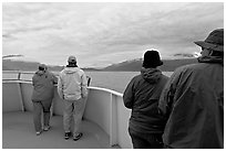 Passengers standing on deck with colorful  clothes. Seward, Alaska, USA ( black and white)