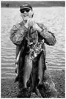 Man carrying salmon freshly caught in the Fishing Hole. Homer, Alaska, USA (black and white)