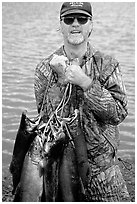 Fisherman carrying salmon freshly caught in the Fishing Hole. Homer, Alaska, USA (black and white)