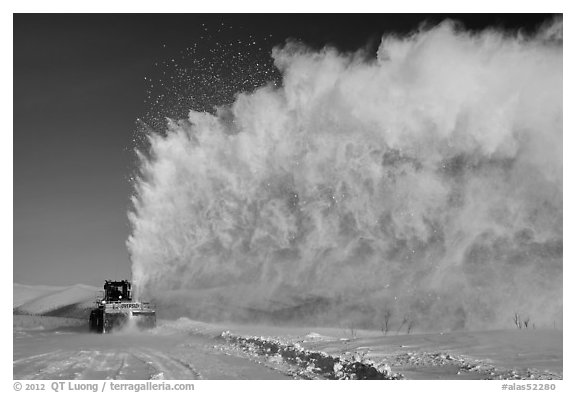 Snow plow truck with cloud of snow. Alaska, USA