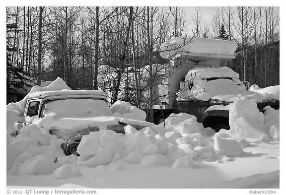 Trucks covered with piles of snow. Wiseman, Alaska, USA