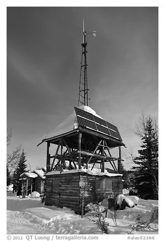 Tower with solar panels and windmill. Wiseman, Alaska, USA