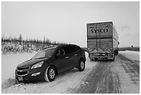 Commercial truck towing car, Dalton Highway. Alaska, USA ( black and white)