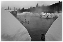 Soaking in natural hot pool surrounded by snow. Chena Hot Springs, Alaska, USA (black and white)