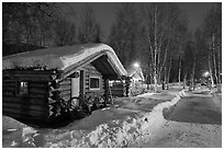 Path in snow and cabins at night. Chena Hot Springs, Alaska, USA (black and white)