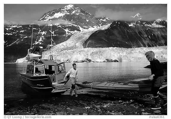 Kayakers unload  kayak from  water taxi boat at Black Sand Beach. Prince William Sound, Alaska, USA (black and white)