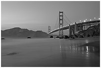Golden Gage bridge at dusk, reflected in wet sand at East Baker Beach. San Francisco, California, USA (black and white)
