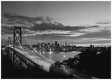 Bay Bridge and city skyline with lights at sunset. San Francisco, California, USA (black and white)