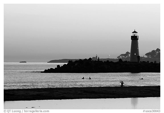 Lighthouse and Surfers in the water at sunset. Santa Cruz, California, USA