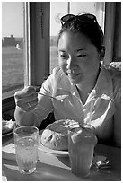 Woman eating a bown of clam chowder on the pier. Santa Cruz, California, USA ( black and white)