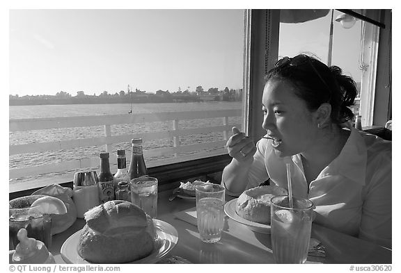Woman eating clam chowder in a sourdough bread bowl. Santa Cruz, California, USA (black and white)