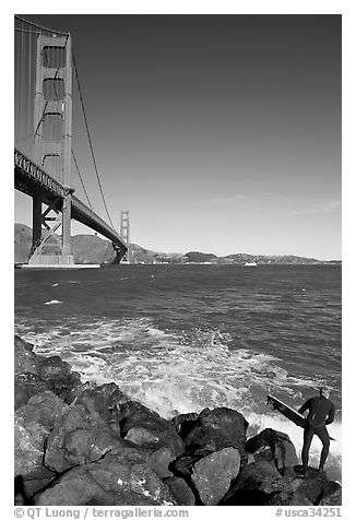 Surfer poised to jump in water below the Golden Gate Bridge. San Francisco, California, USA