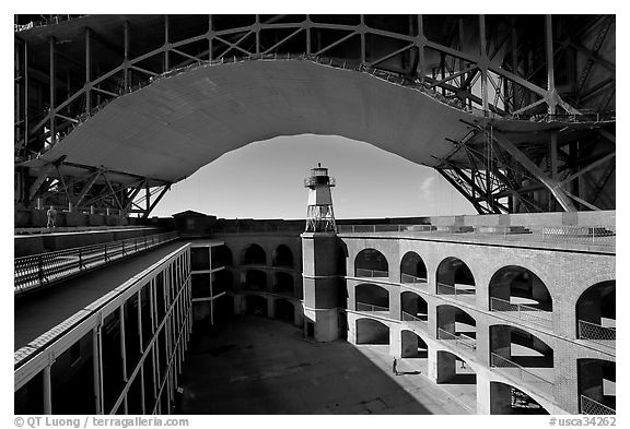 Fort Point courtyard, lighthouse,  and arch of the Golden Gate Bridge. San Francisco, California, USA (black and white)