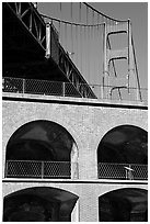 Arched galleries of Fort Point and Golden Gate Bridge pillar. San Francisco, California, USA (black and white)