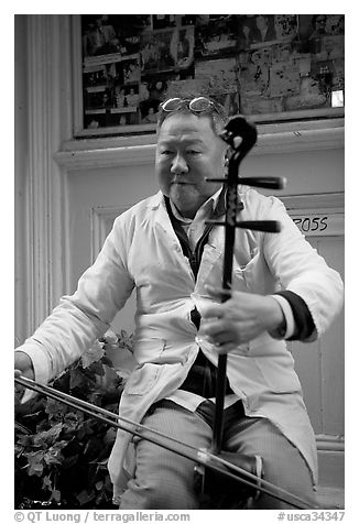 Chinese man playing the traditional Ehru, Chinatown. San Francisco, California, USA
