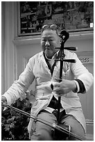 Chinese man playing the traditional Ehru, Chinatown. San Francisco, California, USA (black and white)