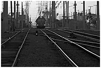 Railroad tracks, train, and power lines, sunrise. San Diego, California, USA ( black and white)