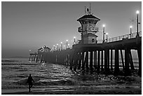 Surfer and Huntington Pier lights at twilight. Huntington Beach, Orange County, California, USA (black and white)