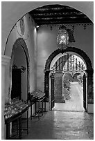 Corridor with candles next to the Serra Chapel. San Juan Capistrano, Orange County, California, USA (black and white)