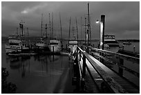 Deck and boats at night. Morro Bay, USA ( black and white)